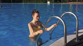Una donna attraente con una buona figura emerge da una piscina all'aperto video d archivio