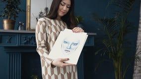 Una donna attraente dello stilista della ragazza che lavora in uno studio di arte Una giovane donna mostra gli schizzi delle prog stock footage