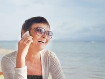 Una donna attraente di 50 anni con un telefono cellulare Fotografie Stock