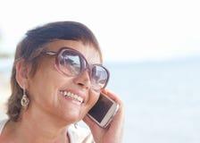 Una donna attraente di 50 anni con un telefono cellulare Immagine Stock Libera da Diritti