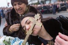 Una donna bacia un incrocio di legno recuperato dal mare durante Immagini Stock Libere da Diritti