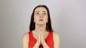 Una donna bella giovane prega, chiedendo Dio l'aiuto archivi video