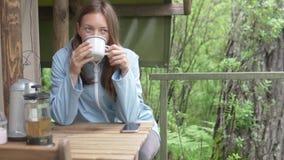 Una donna beve il tè di mattina nel legno vicino alla tenda video d archivio