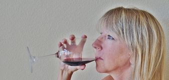 Una donna bionda che beve un vino rosso di vetro o. Immagini Stock Libere da Diritti