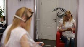Una donna bionda che pratica il surfing Internet con il suo smartphone nello studio dei capelli archivi video