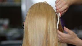 Una donna bionda nello studio dei capelli video d archivio