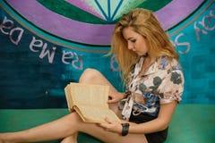 Una donna bionda sta leggendo un libro su uno strato Fotografia Stock Libera da Diritti