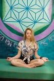Una donna bionda sta meditando su strato Fotografia Stock