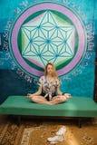 Una donna bionda sta meditando su strato Immagini Stock