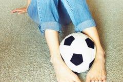 Una donna in blue jeans con una palla di calcio di calcio immagine stock