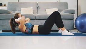 Una donna in buona salute che fa esercizio fisico con abbigliamento atletico e che si prepara a casa Stile di vita sano video d archivio