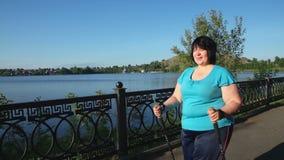 Una donna cammina attraverso il parco con i bastoni, su una mattina soleggiata dell'estate archivi video