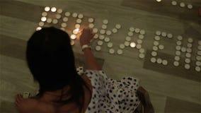 Una donna castana che accende le candele sul pavimento stock footage