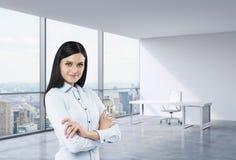 Una donna castana in un posto di lavoro all'ufficio panoramico d'angolo moderno a New York, Manhattan Un concetto del consulti fi Immagini Stock