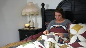 Una donna caucasica che legge un libro a letto stock footage
