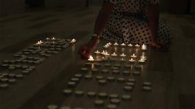 Una donna che accende le candele sul pavimento archivi video