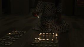 Una donna che accende una partita per accendere le candele stock footage