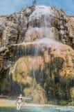 Una donna che bagna la cascata Giordano delle sorgenti di acqua calda del ma'in Fotografia Stock Libera da Diritti
