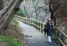 Una donna che cammina & che cattura le fotografie sulla pista Fotografie Stock