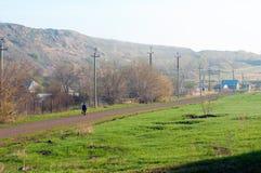 Una donna che cammina dalla stazione nel suo villaggio fotografia stock