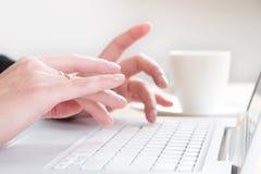 Una donna che digita su un computer portatile Fotografia Stock