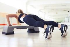 Una donna che esercita esercizio aerobico di forma fisica di allenamento per il abdomi Immagini Stock