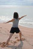 Una donna che fa l'yoga si esercita su una spiaggia fotografie stock