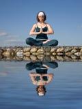 Una donna che fa yoga su una pietra al disopra della superficie Immagine Stock Libera da Diritti