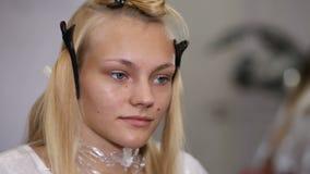 Una donna che ha suo taglio di capelli in studio video d archivio
