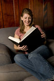 Una donna che legge un grande libro Immagine Stock