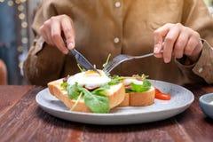 Una donna che mangia il panino della prima colazione con le uova, il bacon e la panna acida dal coltello e la forcella in un piat immagine stock libera da diritti