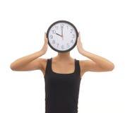 Una donna che nasconde il suo fronte dietro un orologio Fotografie Stock