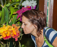 Una donna che odora un'orchidea Immagini Stock