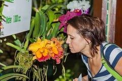 Una donna che odora un'orchidea Fotografia Stock Libera da Diritti