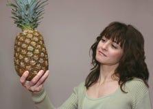 Una donna che osserva un ananas Fotografie Stock Libere da Diritti
