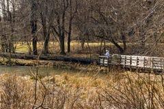 Una donna che pesca per la trota da un sentiero costiero immagini stock