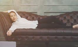 Una donna che porta una camicia bianca sta dormendo immagine stock