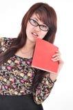 Una donna che porta un libro rosso Fotografie Stock Libere da Diritti