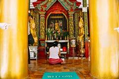 Una donna che prega in un tempio alla pagoda di Shwedagon in Rangoon Immagini Stock