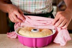 Una donna che prende l'asciugamano fuori dal rollè sollevato della pasta di lievito Fotografie Stock Libere da Diritti