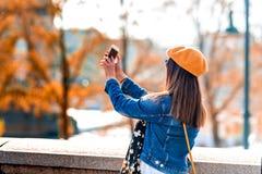 Una donna che prende le immagini in un parco della città immagini stock