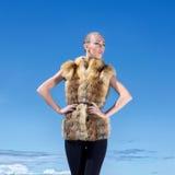 Una donna che propone in un rivestimento della pelliccia su una priorità bassa del cielo Fotografia Stock