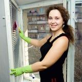 Una donna che pulisce una finestra Fotografie Stock Libere da Diritti