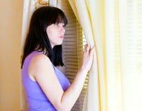 Una donna che si leva in piedi alla finestra Immagini Stock