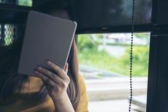 Una donna che si siede dalla finestra di vetro che guarda, per mezzo e tenente del pc della compressa copre il suo fronte Fotografie Stock Libere da Diritti