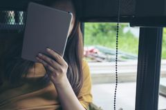 Una donna che si siede dalla finestra di vetro che guarda, per mezzo e tenente del pc della compressa copre il suo fronte Immagini Stock Libere da Diritti