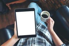 Una donna che si siede il pc nero fornito di gambe e di tenuta trasversale della compressa con lo schermo da tavolino bianco in b Fotografie Stock