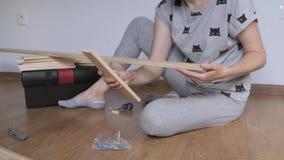 Una donna che si siede in una stanza sul pavimento disimballa uno scaffale di legno comprato nel deposito Montaggio di mobilia stock footage