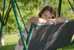 Una donna che si siede su un'oscillazione Immagini Stock