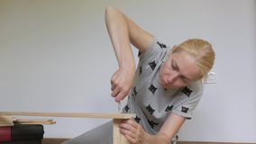 Una donna che si siede sul pavimento raccoglie la mobilia di legno nella stanza, torce le viti con un cacciavite video d archivio